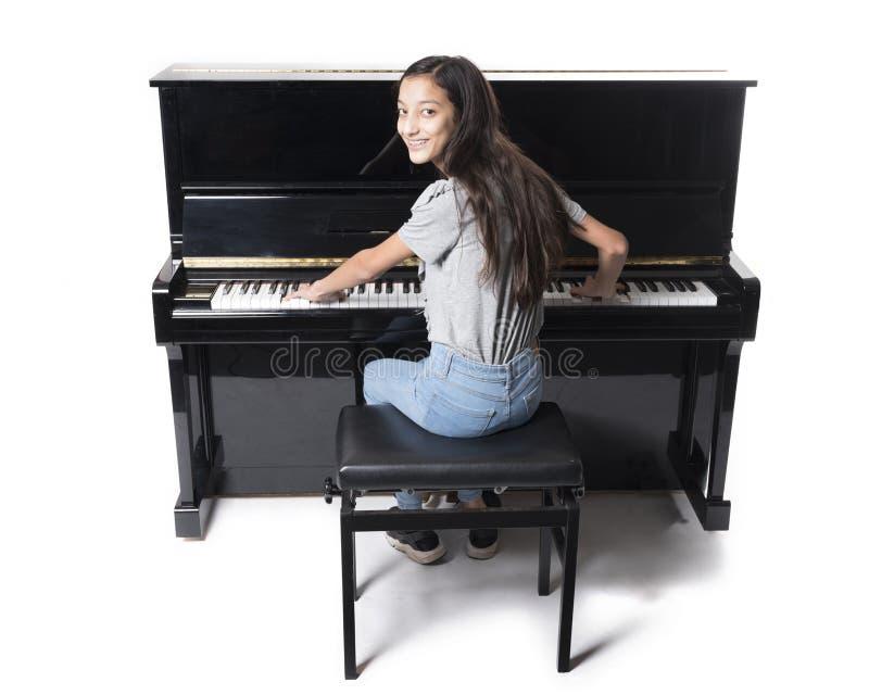 少年深色的女孩和黑大钢琴在演播室 免版税库存照片