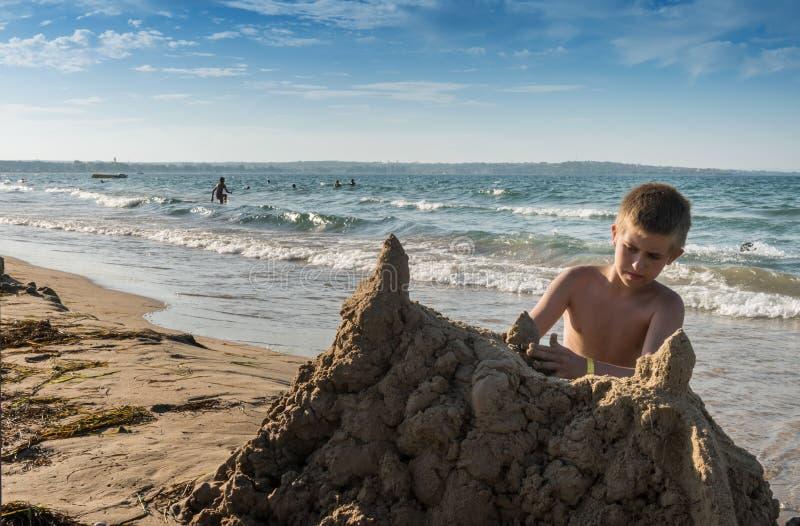 少年男孩修造大沙子城堡 免版税库存图片