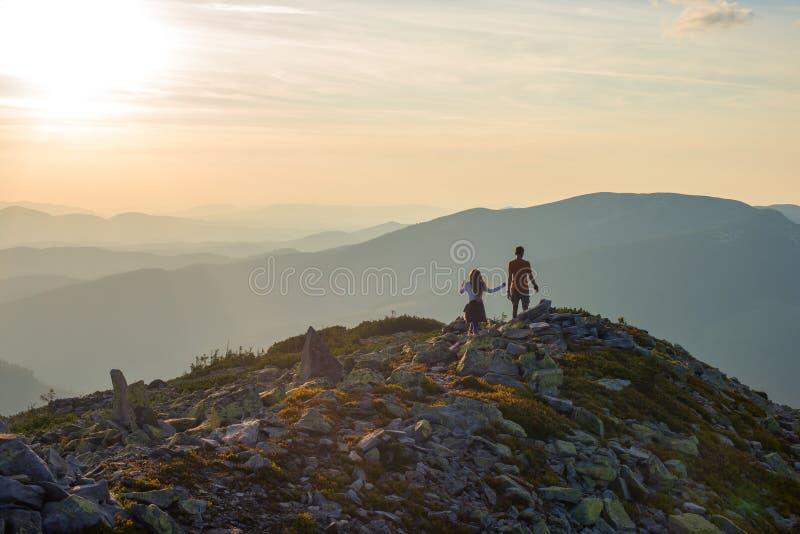少年男孩和女孩沿石山脉走 免版税图库摄影