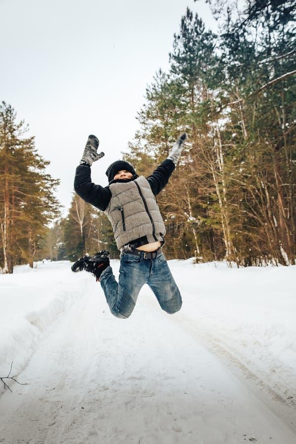 少年男孩获得乐趣在冬天森林 库存照片