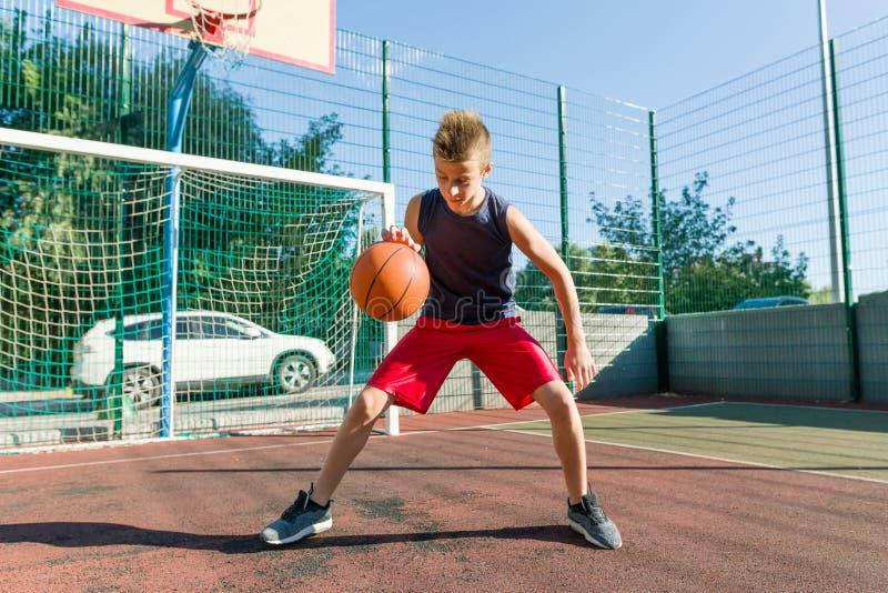 少年男孩街道城市篮球场的蓝球运动员 免版税库存照片