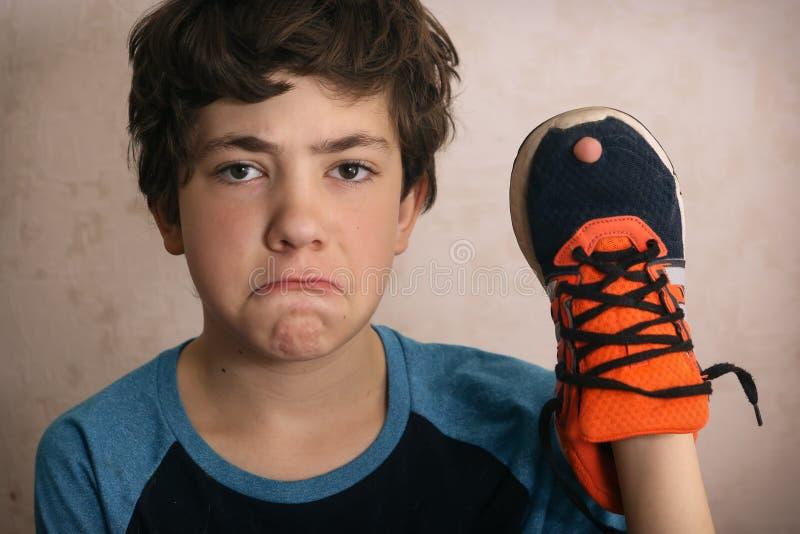 少年男孩被挫败关于在他喜爱的教练员鞋子的孔 库存照片
