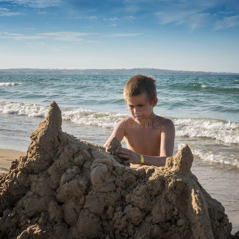 少年的方形的图象有大沙子城堡的 库存图片