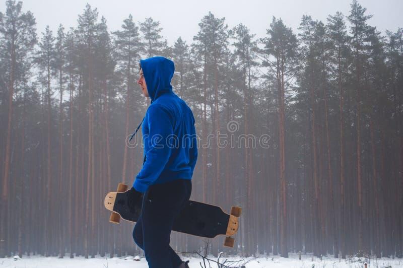 少年的特写镜头,站立在握一个滑板的手的在一个冬天的背景的蓝色运动衫 免版税库存照片