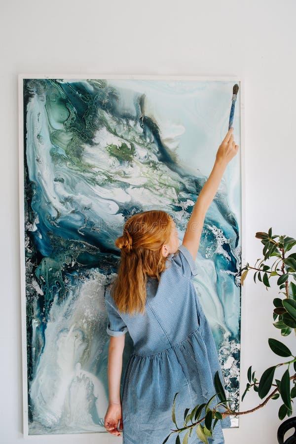 少年红头发人女孩在垂悬在墙壁上的帆布绘 免版税库存图片