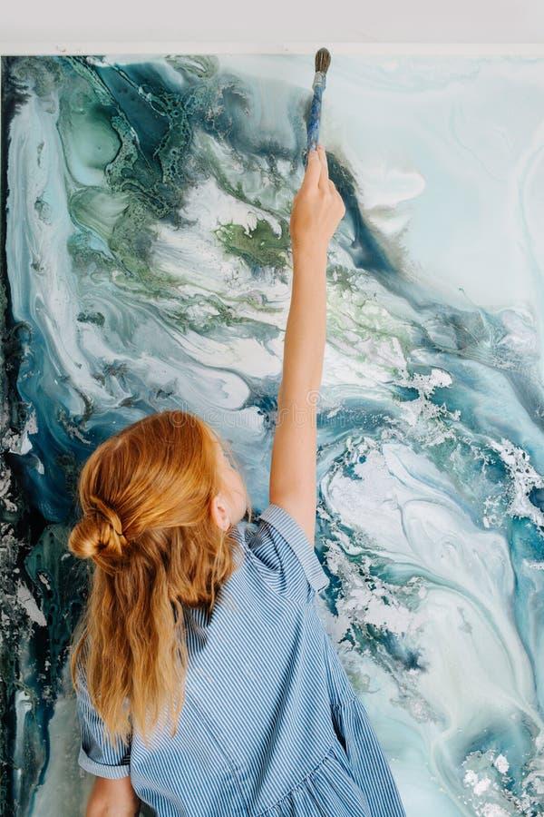 少年红头发人女孩在垂悬在墙壁上的帆布绘 免版税图库摄影