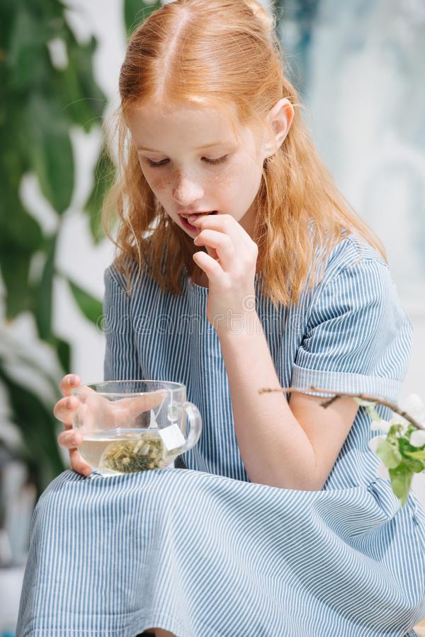 少年红头发人女孩坐箱子,饮用的茶并且吃着曲奇饼 免版税库存图片