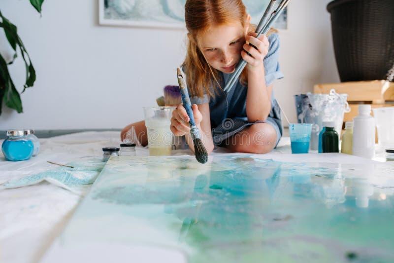 少年红头发人女孩绘与在大帆布的刷子在地板上在车间 免版税库存照片