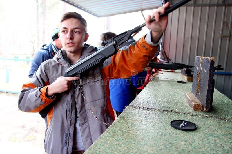 少年给在靶场户外的一杆步枪充电 免版税库存照片