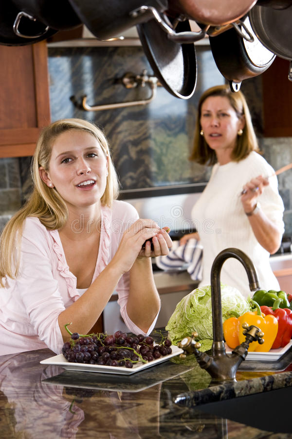 少年聊天的女孩厨房的母亲 库存照片