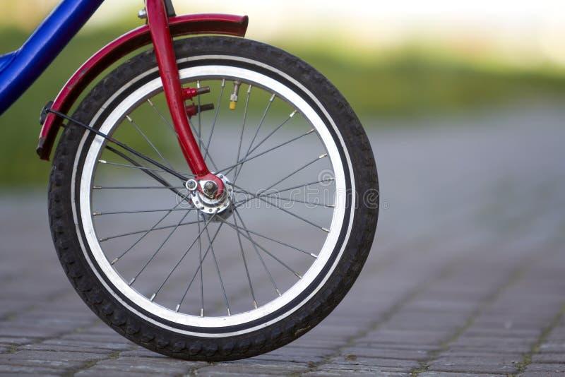 少年自行车前轮特写镜头细节在灰色路面的在明亮的晴天弄脏了bokeh背景 都市舒适的t 库存照片