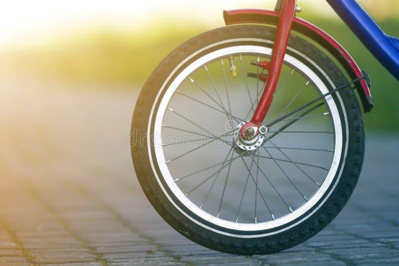 少年自行车前轮特写镜头细节在灰色路面的在明亮的晴天弄脏了bokeh背景 都市舒适 免版税库存照片