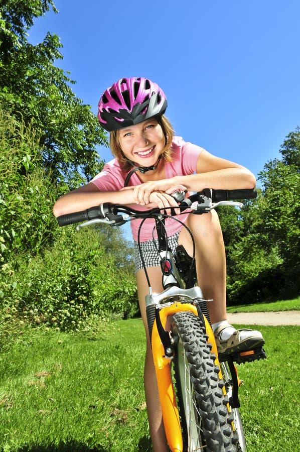 少年自行车的女孩 免版税库存照片