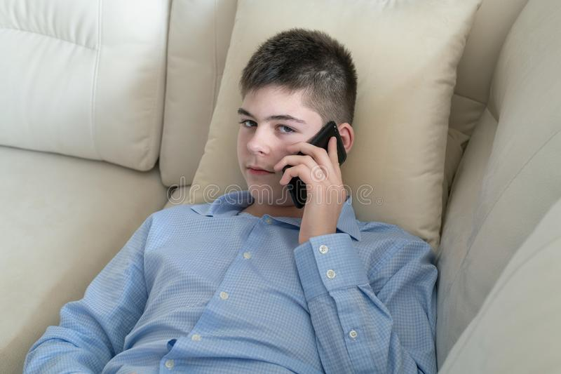 少年谈话在说谎在沙发的手机 免版税图库摄影