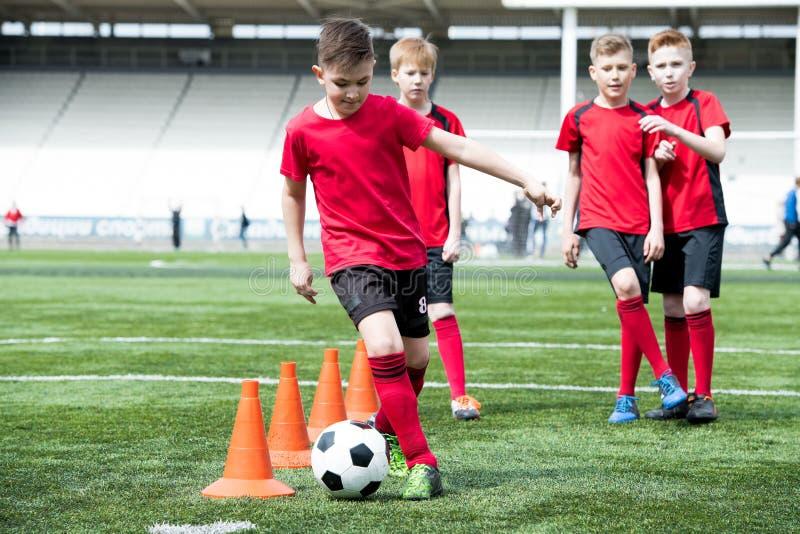 少年足球运动员主导的球 免版税库存照片