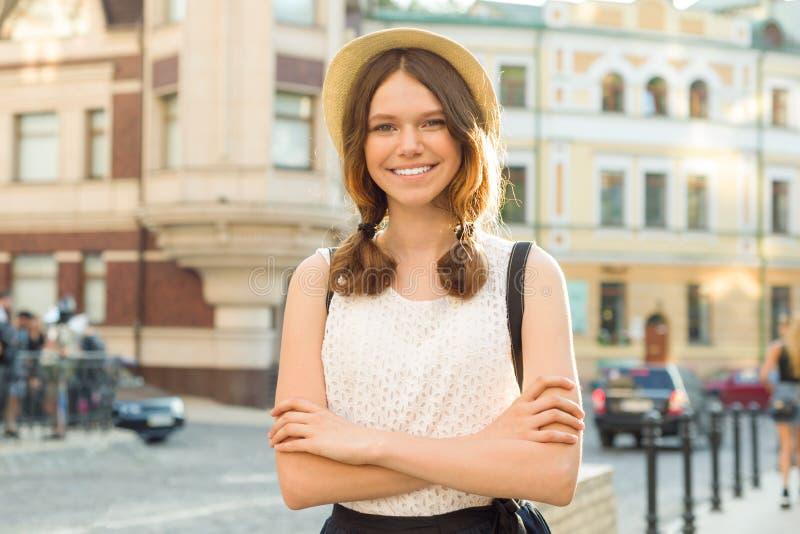 少年13, 14岁,有横渡的胳膊的女孩,城市街道背景室外画象  免版税图库摄影