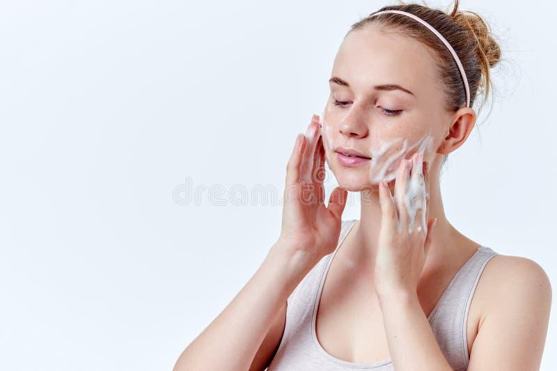 少年skincare 有雀斑和蓝眼睛的美丽的十几岁的女孩使用起泡沫的清洁剂 面孔洗涤物 免版税库存照片
