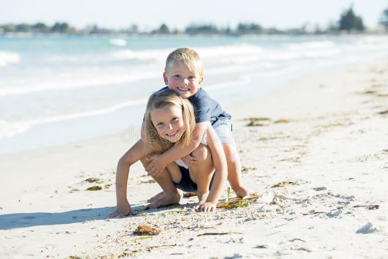 少许一起使用在与拥抱他美丽的白肤金发的年轻姐妹enjo的小兄弟的沙子海滩的可爱和甜兄弟姐妹 图库摄影