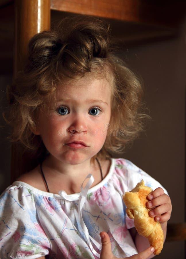 少许吃女孩的新月形面包 免版税库存图片