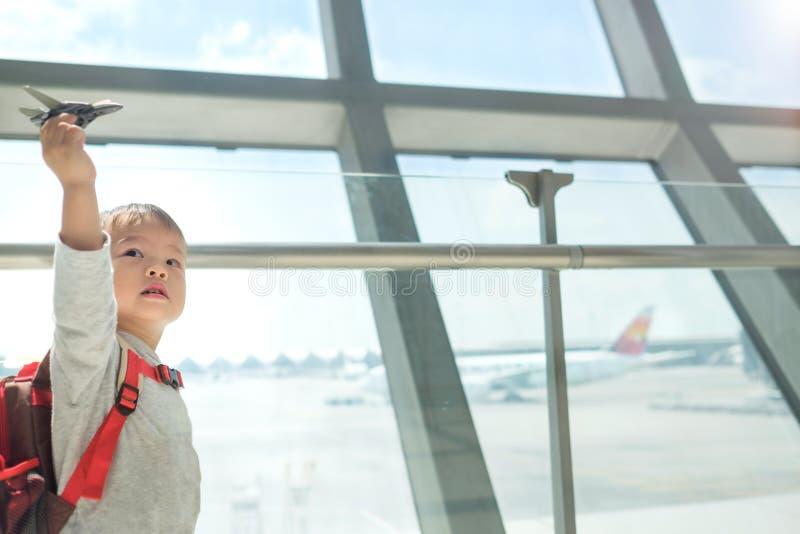少许微笑亚洲人2岁小孩获得男孩的儿童使用与飞机玩具的乐趣,当等待他的飞行在机场时 库存照片