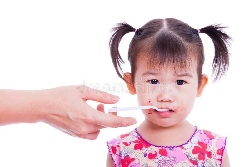 少许拿着在嘴的亚裔(泰国)女孩匙子 免版税图库摄影