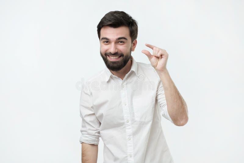 少许显示某事用手的英俊的西班牙人,当打手势和广泛地微笑时 免版税库存图片