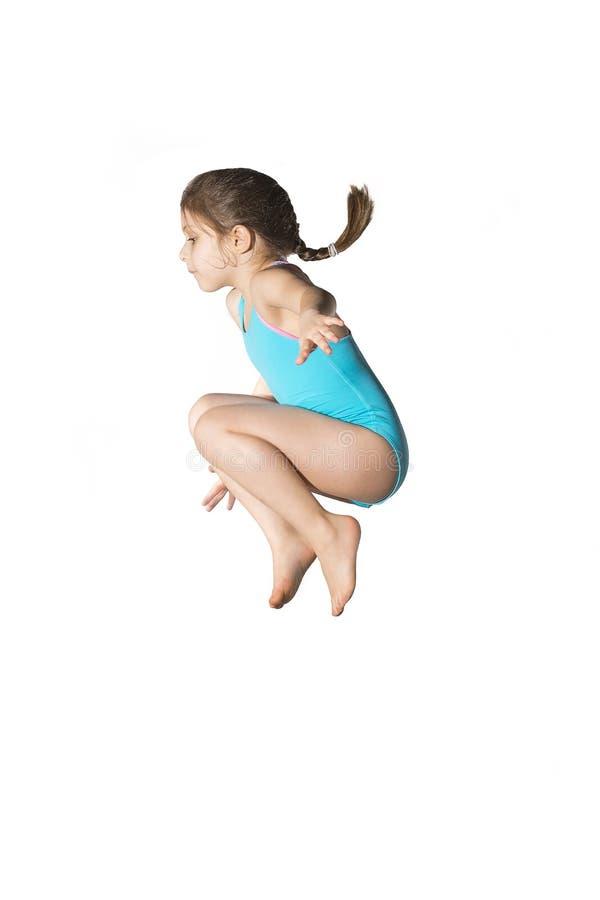 少许白种人女性7岁跳跃在白色背景的深蓝游泳衣的女孩 库存照片