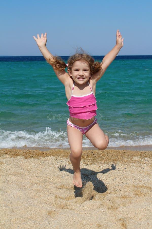少许跳海滩的女孩 免版税库存照片
