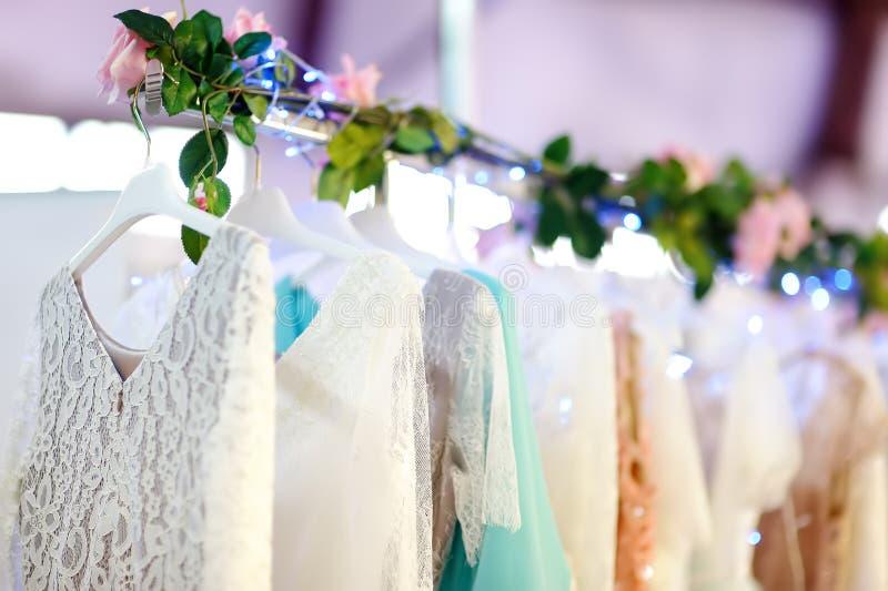 少量典雅的婚礼、女傧相、晚上、舞会礼服或者正式舞会礼服在一个挂衣架在一家新娘商店 免版税图库摄影