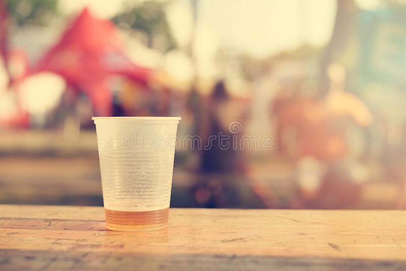 少量在塑料杯子的啤酒在木桌上 免版税库存照片
