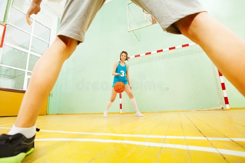 少年亚裔在法院的女孩滴下的篮球 免版税图库摄影