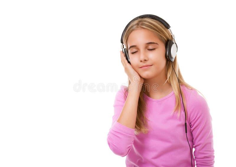 少年可爱的女孩的图片有耳机听的音乐的,被隔绝 免版税图库摄影