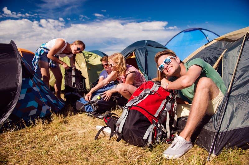 少年坐在帐篷前面的地面 免版税库存图片