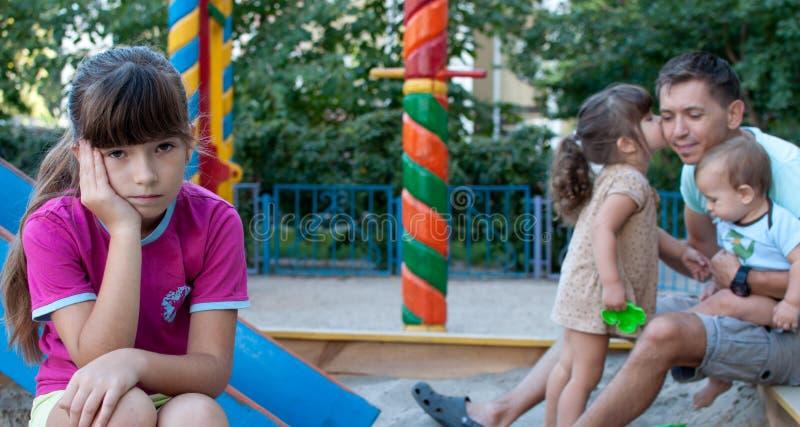 少年女孩嫉妒她的妹妹和兄弟 图库摄影