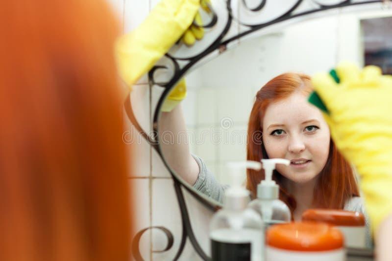 少年女孩清洗镜子 免版税图库摄影