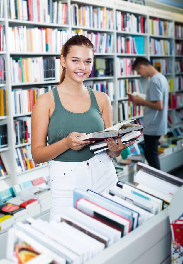 少年女孩阅读书,当选择新的文学时 库存照片