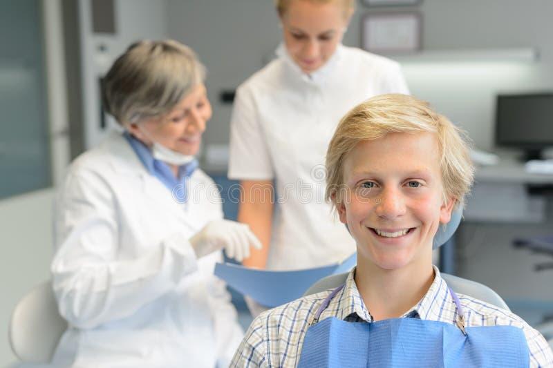 少年患者,有牙科助理的牙医妇女 免版税库存照片