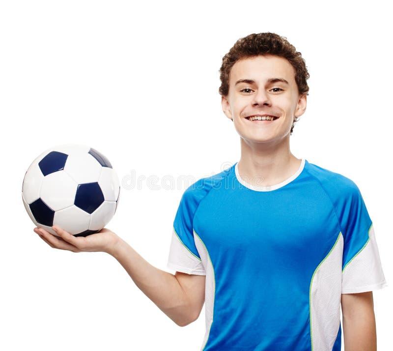 少年拿着球的足球运动员 免版税库存照片