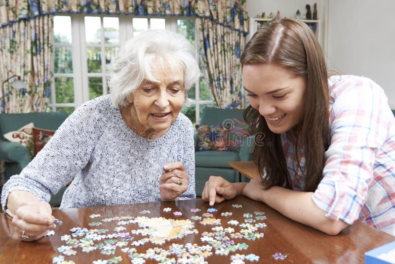 少年有七巧板的孙女帮助的祖母 免版税库存图片