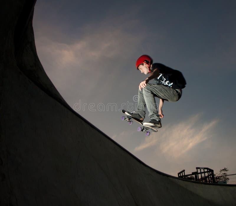少年从滑板管跳 库存图片