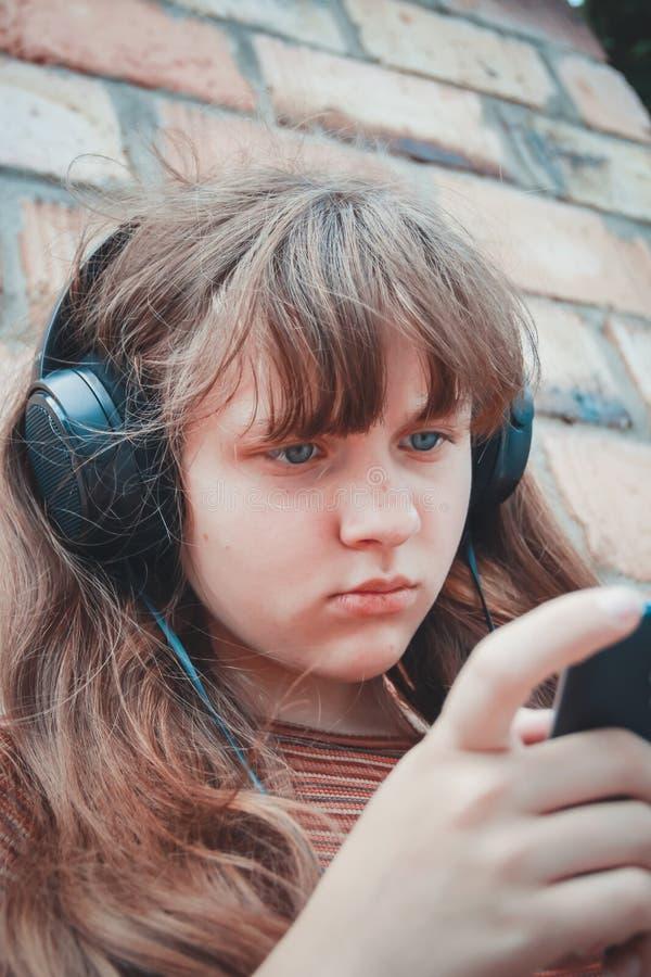 少年概念-有耳机的十几岁的女孩听到音乐的外面 免版税库存照片