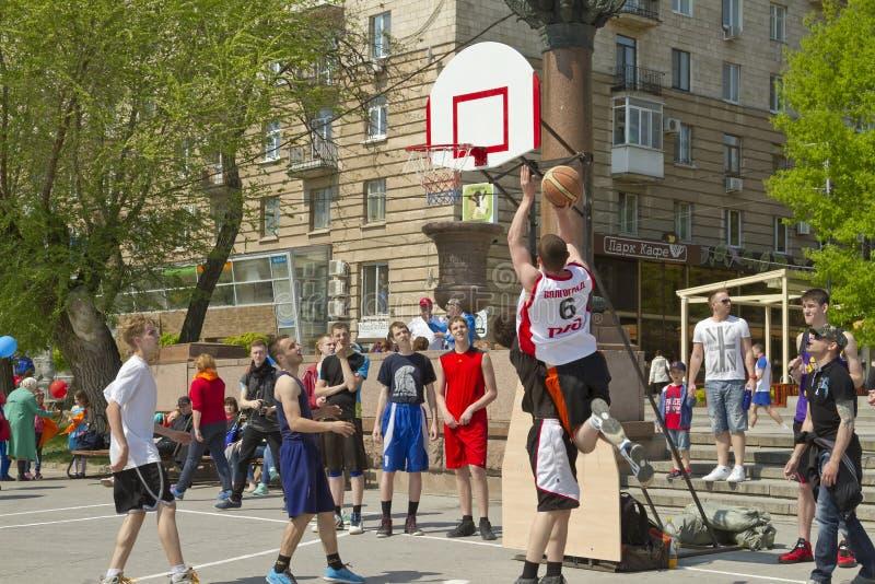 少年演奏在露天沥青地面的streetball 免版税库存图片