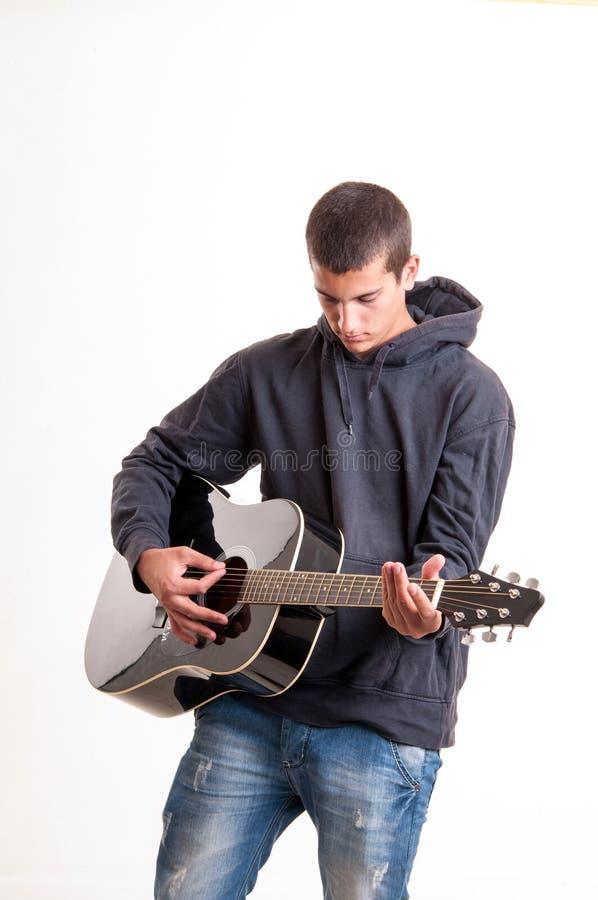 少年男孩使用在充满感觉的声学吉他 免版税库存图片
