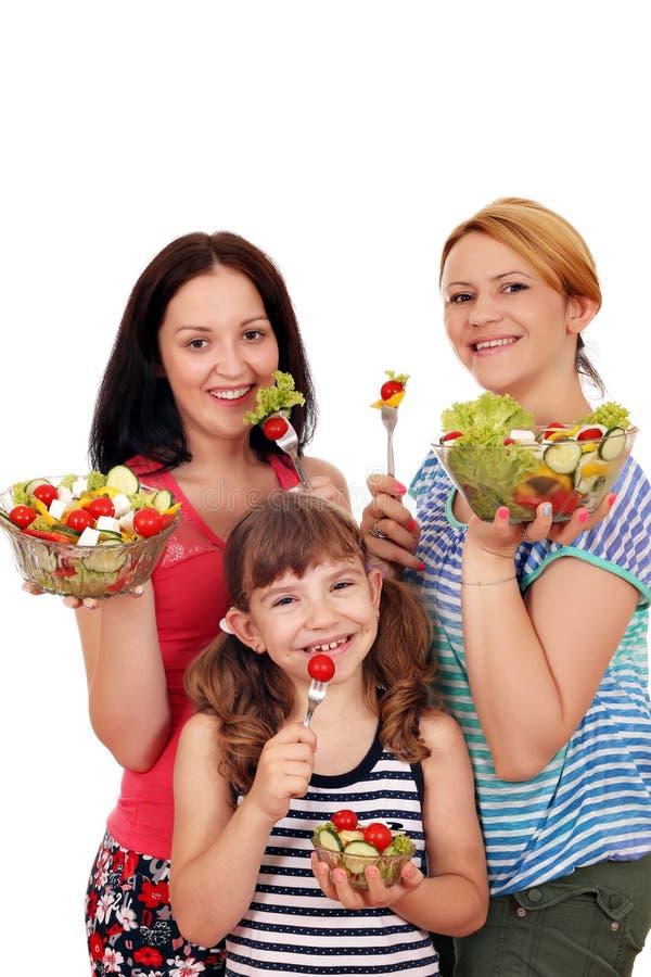 少年的妇女和小女孩吃沙拉 库存图片