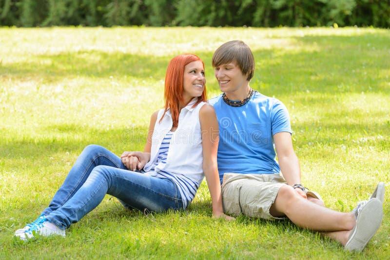 少年看的夫妇坐的草 免版税库存照片