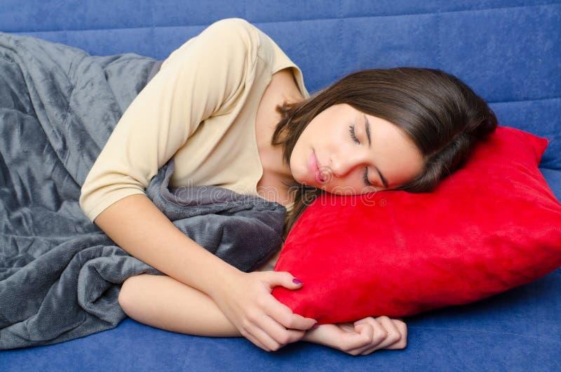 少年美丽的女孩休眠的沙发 库存照片