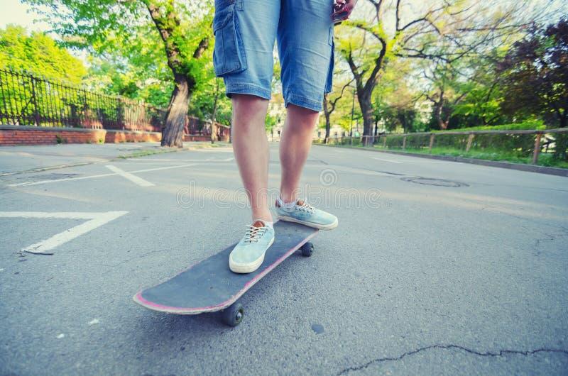 少年腿和滑板在路在夏天 免版税库存图片