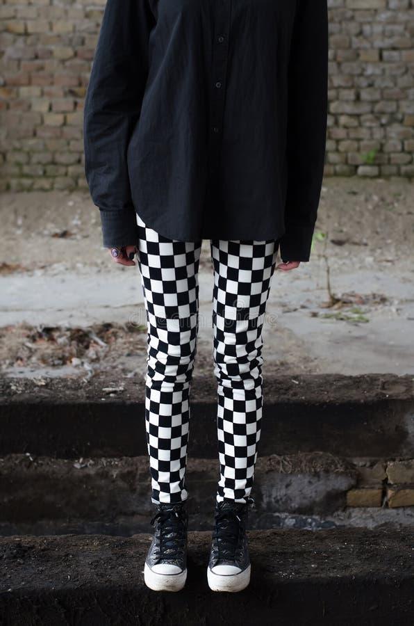 少年goth女孩长的腿和运动鞋  库存照片