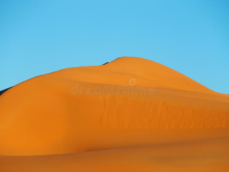 尔格CHEBBI沙丘峰顶在MERZOUGA附近的与含沙沙漠形成风景在东南摩洛哥 库存图片