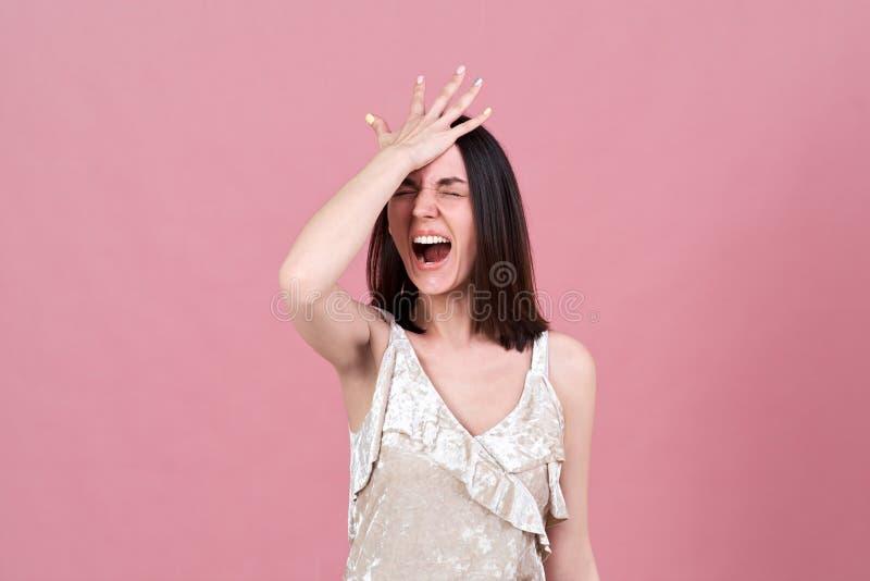 尖叫从重音和按她的棕榈的一名年轻可爱的深色的妇女的演播室画象对她的头 免版税库存图片